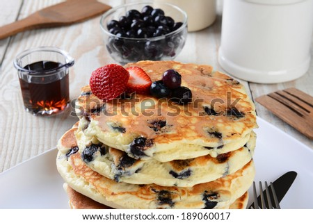 Blueberry Pancake Closeup with syrup pitcher, wooden spatula and fork, blueberry bowl and other items set out for a homemade breakfast. Horizontal format. - stock photo