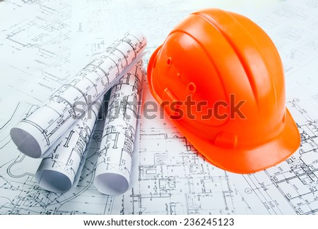 Blueprint rols and helmet - stock photo