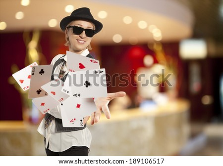 Bluff, happy blonde woman in cap playing with poker cards - stock photo