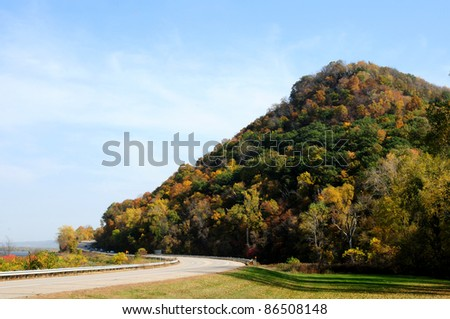 Bluff in fall colors along highway and Mississippi River at Lake Pepin, Minnesota - stock photo
