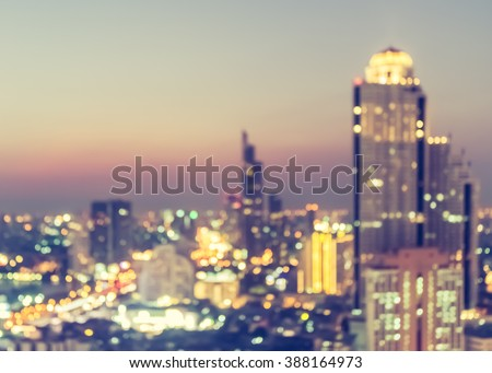 Blur abstract background aerial view of Bangkok cbd downtown city night light colorful bokeh hazy warm gold golden hour orange tone: Central business district on electric train line, road over river - stock photo