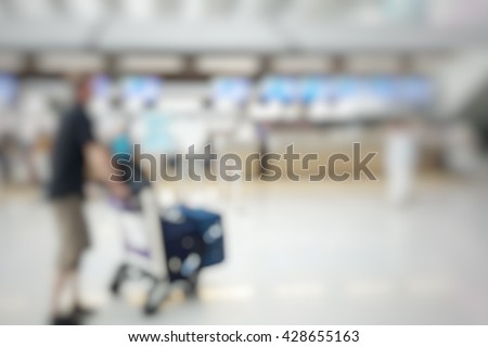 Blur abstract background bokeh of Terminal Departure Check-in at airport. Blurry view of check in counter row with passenger with trolley travelling by plane at air port.International airport interior - stock photo