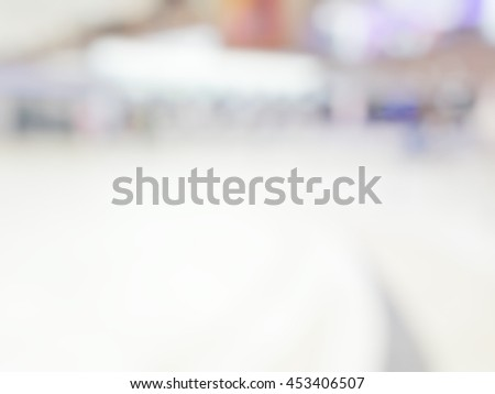 Blur abstract background of travellers waiting for luggage in baggage claim at international airport. Blurry view people wait at checking in to go aboard in terminal hall bokeh effect. - stock photo