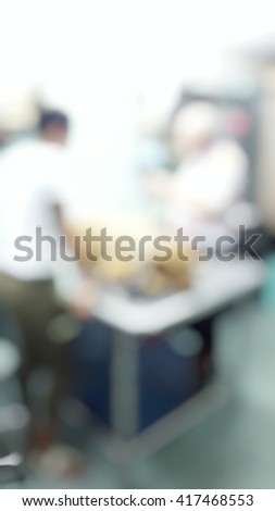 Blur abstract background of veterinarian giving treatment to sick Labrador dog. Blurry view vet treat brown dog  on a drip receiving a saline solution. - stock photo
