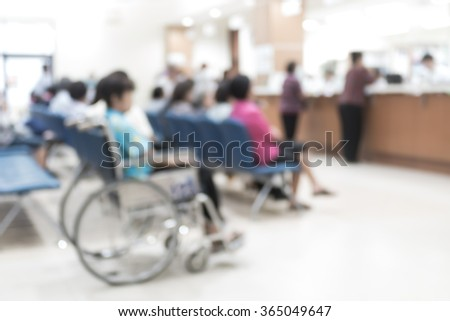 Blur abstract background perspective view of wheelchair seat row in hospital building interior/ clinical hallway indoor area w/ visitors patients waiting to see doctors, people paying money at cashier - stock photo