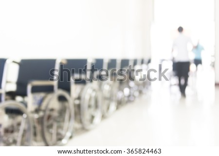Blur abstract background perspective view of wheelchair seat row in hospital building interior/ clinical hallway indoor area w/ people visitors patients waiting to see doctors, nurse staffs working - stock photo