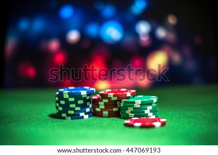 Blur background and chips, Stack of poker chips on a green table. Poker game theme - stock photo