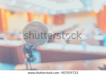 Blur background,close up microphone at podium at Seminar event room with bokeh light ,Business concept. - stock photo