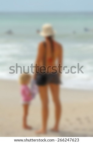 Blur Background Image of a Mother and Daughter on the Beach watching swimmers in the Ocean   - stock photo