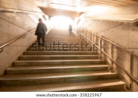 Blur background image of people walking up on concrete stair with light. - stock photo