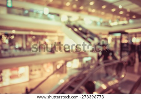 Blur background photograph of people in the department store building with huge escalator in retro color - stock photo