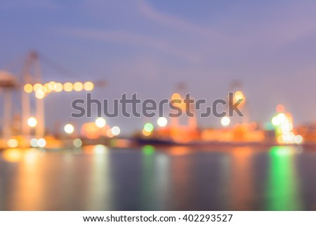 Blur bokeh of harbor with large ship and crane at night - stock photo