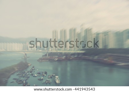 blur city landscape - abstract motion blurred background of Hong Kong highrises and river port - stock photo