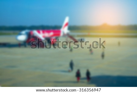 Blur effect of people go to plane with sunset light  - stock photo