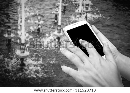 blur hand touching mobile phone with blur water drop from fountain in pool background  ,black and white tone - stock photo