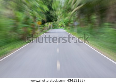 blur high speed road, moving to forest. - stock photo