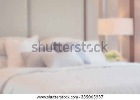 blur image of classic bedroom interior with pillows and reading lamp on bedside table - stock photo