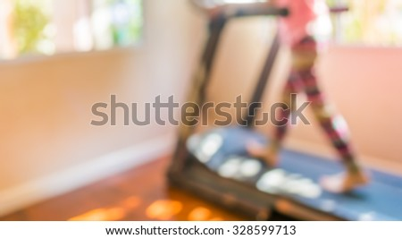 blur image of Cute girl running treadmill on day time for background usage. - stock photo