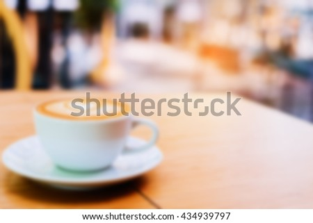 Blur image of hot coffee in coffee shop with vintage tone colour. - stock photo