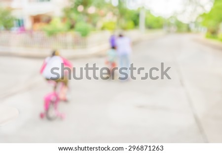 blur image of people riding bike in public park on day time for background usage. - stock photo