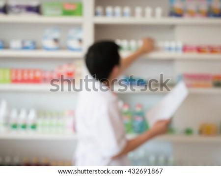 blur image of pharmacist taking medicine from shelf in the pharmacy - stock photo