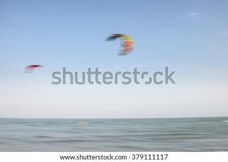 Blur motion abstract people are playing the extreme Sport, Kite Surfer Riding Wave getting Barreled. - stock photo