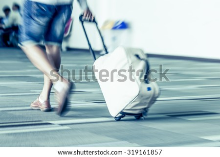 Blur motion of passengers walking at airport in vintage color filter - stock photo