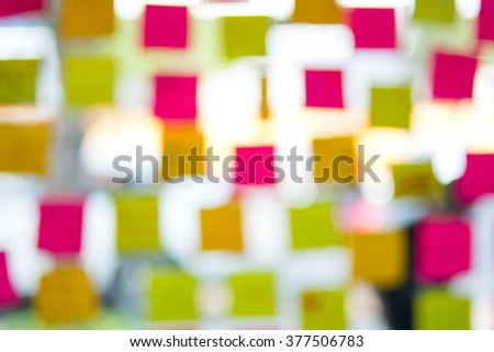 Blur of colorful sticky notes on glass - stock photo