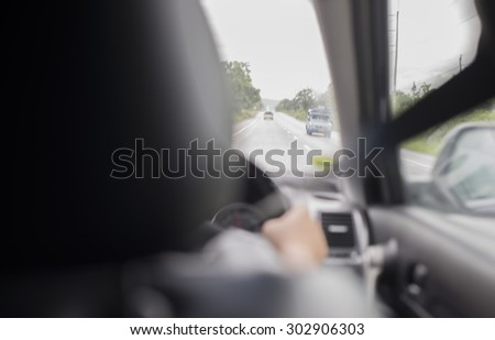 Blur of driver's hands on steering wheel - stock photo