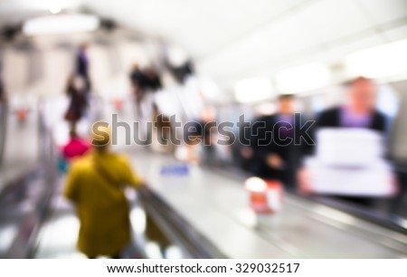 Blur of people going down at escalator, London underground  - stock photo
