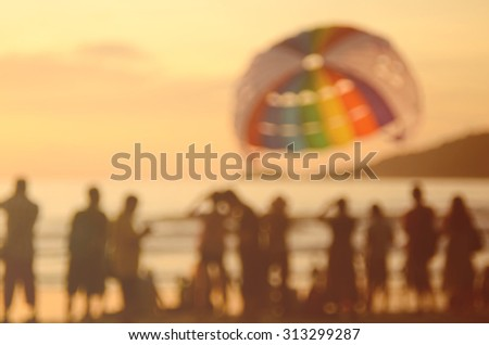 Blur people on tropical sunset beach with parachute boat abstract background. - stock photo
