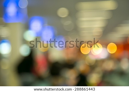 Blur photo of an airport terminal with unrecognizible passengers passing by with luggage. Blurred background for topics of travel and transportation. - stock photo