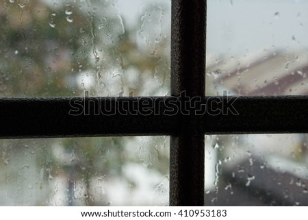 blur raining window with house and tree view outside background - stock photo