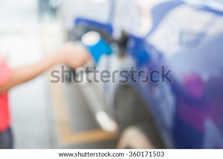 Blur refueling car with gasoline pump  - stock photo