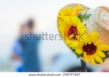 Blur romantic couples, a hat with a sunflower artificial the foreground. - stock photo