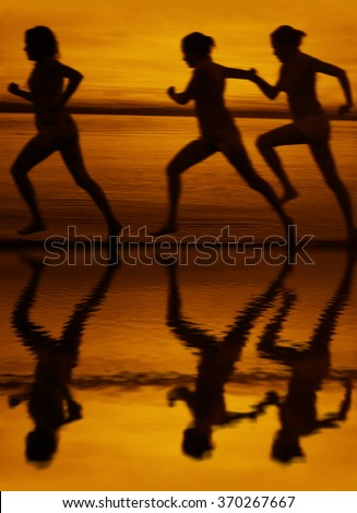 blur silhouette of three women running at sunset or sunrise Girl move along sun set sunny beach Reflection light on water texture lesbian Couple Doing sports exercises against sky with clouds - stock photo