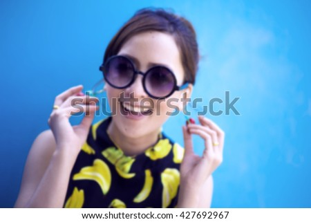 Blur Sunglass Summer girl portrait. Asian woman smiling happy on sunny summer or spring day outside in colourful background. Pretty mixed race Caucasian / Thailand Asian young woman  - stock photo