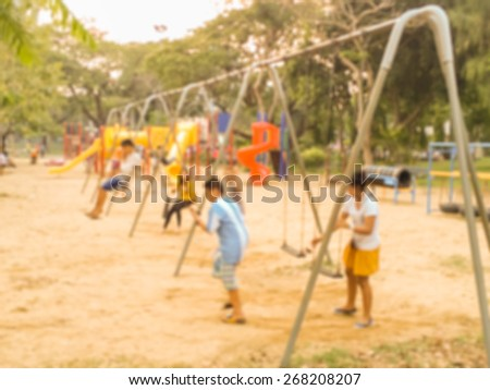 Blur Young Children on Swing in Playground Outdoor in Evening used as Background  - stock photo