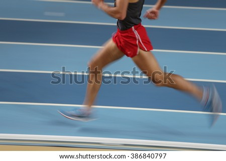Blured athletes run in track and field - stock photo