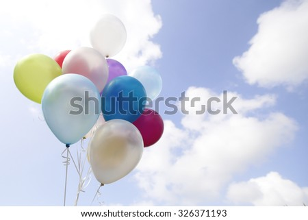 Blured group of colorful balloons with blue sky background - stock photo