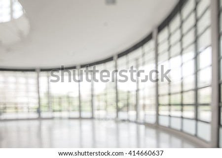 Blurred abstract background interior looking out toward empty office lobby and entrance doors/ transparent glass curtain wall frame: Blurry perspective view reception hall to public building entrance - stock photo