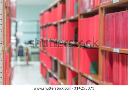 Blurred abstract background of book shelves and interior of college library with textbooks, literature, menuscripts, thesis, magazines, and seating for students and faculties to read     - stock photo