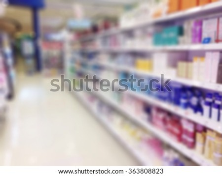 Blurred abstract background of drug store with medicine/ medical/ pharmaceutical/ cosmetic products & supplies arranged on shelves: Blurry interior perspective indoor view inside pharmacy retail shop  - stock photo