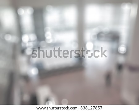 Blurred abstract background of indoor hospital interior in hallway/ lobby waiting area for patients, nurse, doctors and clinic staff circulation in clean, bright and hygienic environment from top view - stock photo