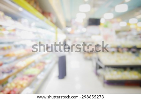blurred abstract background of people shopping in supermarket with miscellaneous product on shelves - stock photo