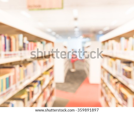 Blurred abstract background of public library interior with aisle of bookshelf with textbooks, literature, magazines. Female student is selecting books from bookshelf. Self-study education concept  - stock photo