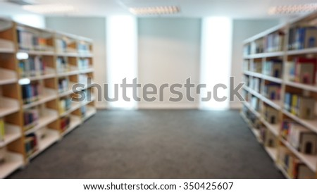 Blurred abstract background of public library interior with aisle of bookshelf with textbooks and furniture for reading area: Blurry perspective view of educational study room space with book shelves - stock photo