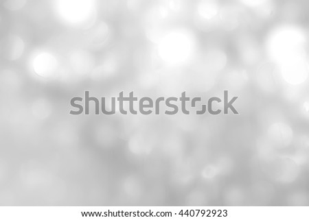 Blurred abstract background of reflective silver magical bokeh of mobile chandelier lamp bright white color lighting in vintage tone: Shiny festive holiday sparkling light crystal glass reflection  - stock photo