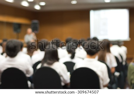 Blurred abstract background of university students sitting in a lecture room with teacher in front of the class with white projector slide screen: Blurry view from back of the classroom: Teachers day  - stock photo