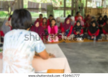 Blurred abstract background of university students sitting in a lecture room with teacher of the out Community education - stock photo